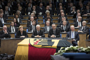 In this handout photo provided by the German Government Press Office (BPA), (L-R) President of the Bundestag Norbert Lammert, Chancellor Angela Merkel, Regional chairman of the Saxony CDU Stanislaw Tillich, President of the Constitutional Court Andreas Vosskuhle and former Foreign Minister of the United States of America James Baker listen during the state memorial ceremony to honor Hans-Dietrich Genscher at World Congress Center on April 17, 2016 in Bonn, Germany. Genscher, a member of the German Free Democrats (FDP), served as German foreign minister from 1974 to 1992 and was widely respected as a shrewd and successful diplomat through the end of the Cold War era.