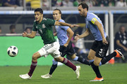 Raul Jimenez #9 of Mexico brings the ball up the field as Diego Godin #3 of Uruguay pursues in the first half during the International Friendly match between Mexico and Uruguay at NRG Stadium on September 7, 2018 in Houston, United States.