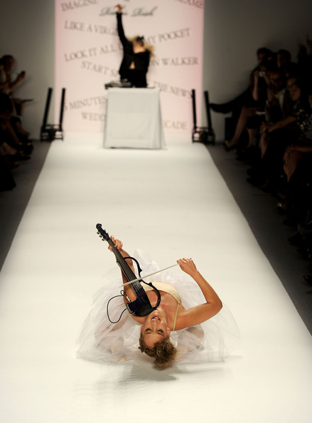 Mia Moretti Violinist Caitlin Moe and DJ Mia Moretti perform on the runway at the Richie Rich Spring 2011 fashion show during Mercedes-Benz Fashion Week at The Studio at Lincoln Center on September 9, 2010 in New York City.