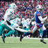 Tyrod Taylor Photos - Tyrod Taylor #5 of the Buffalo Bills runs the ball as Stephone Anthony #44 of the Miami Dolphins attempts to tackle him during the third quarter on December 17, 2017 at New Era Field in Orchard Park, New York. - Miami Dolphins vBuffalo Bills