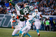 Eric Decker #87 of the New York Jets makes a catch against  Reshad Jones #20, and  Neville Hewitt #46 of the Miami Dolphins in the second quarter during their game at MetLife Stadium on November 29, 2015 in East Rutherford, New Jersey.