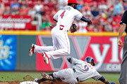 Brandon Phillips #4 of the Cincinnati Reds jumps over Jean Segura #9 of the Milwaukee Brewers to throw out Scooter Gennett #2 of the Milwaukee Brewers to complete a double play during the second inning at Great American Ball Park on July 4, 2015 in Cincinnati, Ohio.
