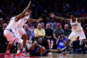 Andrew Wiggins #22 of the Minnesota Timberwolves falls as he is guarded by Sindarius Thornwell #0 and Tyrone Wallace #12 and Lou Williams #23 of the LA Clippers during a 126-118 Timberwolves win at Staples Center on January 22, 2018 in Los Angeles, California.