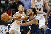Despite losing his balance Derrick Rose #25 of the Minnesota Timberwolves gets off a pass in front of Bryn Forbes #11 of the San Antonio Spurs in season opener at AT&T Center on October 17 , 2018  in San Antonio, Texas.  NOTE TO USER: User expressly acknowledges and agrees that , by downloading and or using this photograph, User is consenting to the terms and conditions of the Getty Images License Agreement.