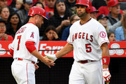 Zack Cozart #7 of shakes hands with Albert Pujols #5 of the Los Angeles Angels of Anaheim after scoring a run in the third inning of the game against the Minnesota Twinsat Angel Stadium on May 12, 2018 in Anaheim, California.