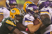 Christian Ponder #7 of the Minnesota Vikings is sacked by Letroy Guion #98 and Mike Daniels #76 of the Green Bay Packers at Lambeau Field on October 2, 2014 in Green Bay, Wisconsin.