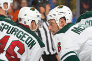 Jared Spurgeon #46 of the Minnesota Wild talks with teammate Cody McCormick #8 during an NHL hockey game against the New York Islanders at Nassau Veterans Memorial Coliseum on March 18, 2014 in Uniondale, New York.