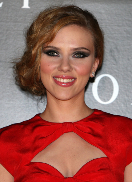 A low chignon pulled over to one side highlights Scarlett's dramatic eye