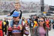 Kyle Busch, driver of the #18 Snickers Almond Toyota, walks with his wife, Samantha, and their son, Brexton, on the grid prior to the Monster Energy NASCAR Cup Series Folds of Honor QuikTrip 500 at Atlanta Motor Speedway on February 25, 2018 in Hampton, Georgia.