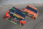 Martin Trruex Jr., driver of thea #78 Bass Pro Shops/5-hour ENERGY Toyota, races Daniel Suarez, driver of the #19 ARRIS Toyota, during the Monster Energy NASCAR Cup Series Hollywood Casino 400 at Kansas Speedway on October 21, 2018 in Kansas City, Kansas.