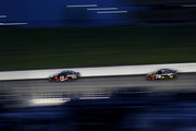 Clint Bowyer, driver of the #14 Haas 30 Years of the VF1 Ford, leads Martin Truex Jr., driver of the #78 5-hour ENERGY/Bass Pro Shops Toyota, during the Monster Energy NASCAR Cup Series KC Masterpiece 400 at Kansas Speedway on May 12, 2018 in Kansas City, Kansas.