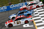 Paul Menard, driver of the #21 Motorcraft /Quick Lane Tire & Auto Center Ford, leads Alex Bowman, driver of the #88 Nationwide Chevrolet, and Brad Keselowski, driver of the #2 Wurth Ford, during the Monster Energy NASCAR Cup Series Pocono 400 at Pocono Raceway on June 3, 2018 in Long Pond, Pennsylvania.