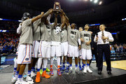 The Florida Gators celebrate with the trophy after defeating the Dayton Flyers 62-52 in the south regional final of the 2014 NCAA Men's Basketball Tournament at the FedExForum on March 29, 2014 in Memphis, Tennessee.