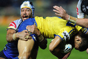 Johnathan Thurston of the Cowboys tackles Ken Sio of the Eels during the round three NRL match between the North Queensland Cowboys and the Parramatta Eels at Dairy Farmers Stadium on March 17, 2012 in Townsville, Australia.