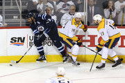 Dustin Byfuglien #33 of the Winnipeg Jets tries to move the puck past Mattias Ekholm #14 and Nick Bonino #13 of the Nashville Predators in Game Six of the Western Conference Second Round during the 2018 NHL Stanley Cup Playoffs on May 7, 2018 at Bell MTS Place in Winnipeg, Manitoba, Canada. (Photo by Jason Halstead /Getty Images) *** Local Caption *** Dustin Byfuglien; Mattias Ekholm; Nick Bonino