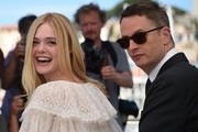 "US actress Elle Fanning (L) laughs while posing on May 20, 2016 with Danish director Nicolas Winding Refn during a photocall for the film ""The Neon Demon"" at the 69th Cannes Film Festival in Cannes, southern France.  / AFP / ANNE-CHRISTINE POUJOULAT"