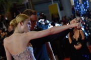 """Danish director Nicolas Winding Refn (R) and US actress Elle Fanning pose as they arrive on May 20, 2016 for the screening of the film """"The Neon Demon"""" at the 69th Cannes Film Festival in Cannes, southern France.  / AFP / LOIC VENANCE"""