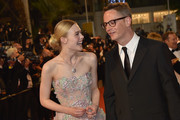 """US actress Elle Fanning (L) laughs with Danish director Nicolas Winding Refn as they arrive on May 20, 2016 for the screening of the film """"The Neon Demon"""" at the 69th Cannes Film Festival in Cannes, southern France.  / AFP / LOIC VENANCE"""