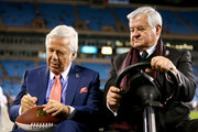(L-R) Chairman and CEO Robert Kraft of the New England Patriots signs a football as he sits with owner/founder Jerry Richardson of the Carolina Panthers before the Patriots take on the Panters at Bank of America Stadium on November 18, 2013 in Charlotte, North Carolina.