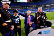 Owner Robert Kraft of the New England Patriots jokes with a young fan as owner Jerry Richardson of the Carolina Panthers signs an autograph before their teams play at Bank of America Stadium on November 18, 2013 in Charlotte, North Carolina.