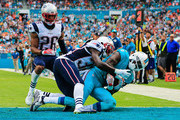 DeVante Parker #11 of the Miami Dolphins scores a touchdown as he is tackled by Devin McCourty #32 of the New England Patriots during the second quarter of the game at Sun Life Stadium on January 3, 2016 in Miami Gardens, Florida.