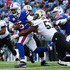 Alex Okafor Photos - Tyrod Taylor #5 of the Buffalo Bills runs with the ball as Alex Okafor #57 of the New Orleans Saints attempts to tackle him during the fourth quarter on November 12, 2017 at New Era Field in Orchard Park, New York. - New Orleans Saints vBuffalo Bills