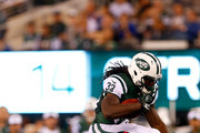 Chris Ivory #33 of the New York Jets leaps over Nat Berhe #34 of the New York Giants during the third quarter of a preseason game at MetLife Stadium on August 22, 2014 in East Rutherford, New Jersey.