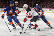 Andy Greene #6 of the New Jersey Devils controls the puck in front of Anders Lee #27 of the Islanders and Josh Bailey #12 of the New York Islanders during the third period at the Prudential Center on February 24, 2018 in Newark, New Jersey. The Devils won 2-1.