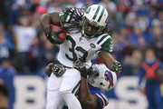Chris Ivory #33 of the New York Jets is tackled as he runs with the ball during NFL game action by Corbin Bryant #97 of the Buffalo Bills at Ralph Wilson Stadium on November 17, 2013 in Orchard Park, New York.