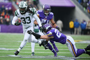 Chris Ivory #33 of the New York Jets advances the ball for a gain while Harrison Smith #22 of the Minnesota Vikings makes the tackle  in the second quarter on December 7, 2014 at TCF Bank Stadium in Minneapolis, Minnesota.