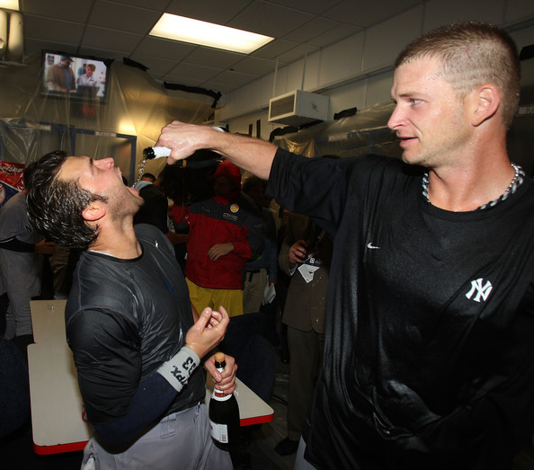 A.J. Burnett (R) of the New York Yankees pours champagne into the mouth of Nick Swisher after a win over the Minnesota Twins in Game Three of the ALDS during the 2009 MLB Playoffs at the Hubert H. Humphrey Metrodome on October 11, 2009 in Minneapolis, Minnesota.