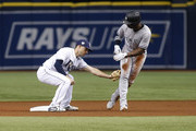 Second baseman Brandon Lowe #35 of the Tampa Bay Rays catches Andrew McCutchen #26 of the New York Yankees attempting to steal second base to end the top of the first inning of a game on September 25, 2018 at Tropicana Field in St. Petersburg, Florida.