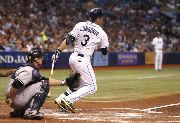 Evan Longoria #3 of the Tampa Bay Rays follows hits a solo home run in front of catcher Brian McCann #34 of the New York Yankees during the fourth inning of a game on September 17, 2014 at Tropicana Field in St. Petersburg, Florida.