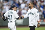 Franklin Gutierrez shakes hands with Ichiro Suzuki #51 of the Seattle Mariners after throwing out the ceremonial first pitch before a game against the New York Yankees at Safeco Field on September 8, 2018 in Seattle, Washington. The Yankees won 4-2.
