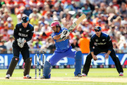 Asghar Stanikzai of Afghanistan bats while Luke Ronchi (L) and Martin Guptill of New Zealand look on during the 2015 ICC Cricket World Cup match between New Zealand and Afghanistan at McLean Park on March 8, 2015 in Napier, New Zealand.