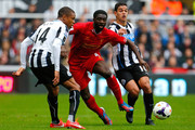 Loic Remy (L) and Hatem Ben Arfa of Newcastle in action with Kolo Toure (C) of Liverpool during the Barclays Premier League match between Newcastle United and Liverpool at St James' Park on October 19, 2013 in Newcastle-Upon-Tyne, England.