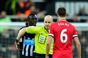 Referee Anthony Taylor steps in as Manchester United player Jonny Evans (c) and Papiss Cisse of Newcastle have words during the Barclays Premier League match between Newcastle United and Manchester United at St James' Park on March 4, 2015 in Newcastle upon Tyne, England.