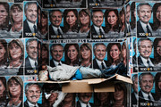 A homeless man sleeps under posters of newly elected president Alberto Fernandez and his running mate Cristina Fernández de Kirchner as people walk through a central business district  the morning after populist was declared the winner in the presidential elections on October 28, 2019 in Buenos Aires, Argentina. The Populist-leaning Fernandez beat out business-friendly incumbent Mauricio Macri in the election that could will have huge consequences for the South American country. With a sharp drop in the peso, high unemployment and rising inflation, Argentines are looking for a leader to steer the economy towards stabilization.
