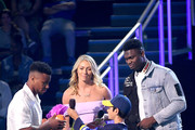 Saquon Barkley accepts the Favorite Breakout Player award from Mikaela Shiffrin and Zion Williamson onstage during Nickelodeon Kids' Choice Sports 2019 at Barker Hangar on July 11, 2019 in Santa Monica, California.