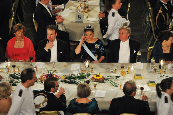 Crown Princess Victoria of Sweden (C) and guests are served food at the Nobel Prize Banquet at Stockholm City Hall on December 10, 2011 in Stockholm, Sweden.