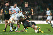 Yannick Nyanga of Racing 92 is tackled by Courtney Lawes during the European Rugby Champions Cup match between Northampton Saints and Racing 92 at Franklin's Gardens on December 18, 2015 in Northampton, England.