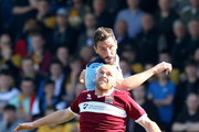 Tom Champion of Cambridge United rises above Jason Taylor of Northampton Town to head the ball during the Sky Bet League Two match between Northampton Town and Cambridge United at Sixfields Stadium on April 6, 2015 in Northampton, England.