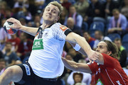 Julius Kuhn of Germany throws the ball against Kent Robin Tonnesen of Norway during the Men's EHF Handball European Championship 2016 match between Germany and Norway at Tauron Arena Hall on January 29, 2016 in Krakow, Poland.