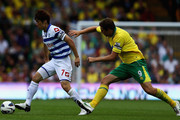 Ji Sung Park of Queens Park Rangers holds off Grant Holt of Norwich during the Barclays Premier League match between Norwich City and Queens Park Rangers at Carrow Road on August 25, 2012 in Norwich, England.