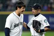 Former Seattle Mariners starting pitcher Hisahsi Iwakuma (L) engages with Ichiro Suzuki #51 of the Seattle Mariners after throwing out the ceremonial first pitch prior to the Seattle Mariners taking on the Oakland Athletics during their game at Safeco Field on September 26, 2018 in Seattle, Washington.