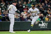 Khris Davis #2 high fives Matt Williams #4 of the Oakland Athletics after hitting a solo home run against the Seattle Mariners in the seventh inning during their game at Safeco Field on September 26, 2018 in Seattle, Washington.