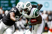 Chris Ivory #33 of the New York Jets runs the ball against  Antonio Smith #94 of the Oakland Raiders during the first quarter at MetLife Stadium on September 7, 2014 in East Rutherford, New Jersey.