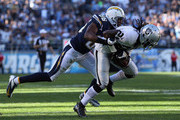 Cornerback Mike Jenkins #21 of the Oakland Raiders is brought down by wide receiver Vincent Brown #86 of the San Diego Chargers after intercepting a pass in the first half at Qualcomm Stadium on December 22, 2013 in San Diego, California. The Chargers defeated the Raiders 26-13.