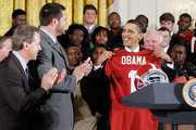U.S. President Barack Obama (R) receives a jersey as head coach Nick Saban (L) and offenisve line Mike Johnson (2nd L) look on during an East Room event to host members of the Alabama Crimson Tide March 8, 2010 at the White House in Washington, DC. Obama welcomed the 2009 BCS Champions to honor its 13th championship and an undefeated season.