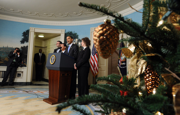 (AFP OUT) Christmas decorations hang from a tree as U.S. President Barack Obama makes a statement on the SAVE (Securing Americans Value and Efficiency)  program in the Diplomatic Reception Room of the White House on December 21, 2009 in Washington, DC. The award is given to Federal employees who submit ideas for saving the government money. He also applauded the Senate's vote to end a Republican filibuster aimed at blocking health care reform.